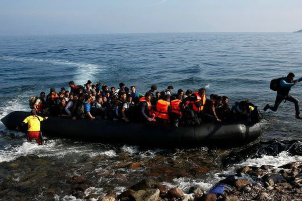 Un migrant afghan sautant du bateau pour rejoindre l'île grecque de Lesbos. 19 octobre 2015. © Yannis Behrakis / Reuters