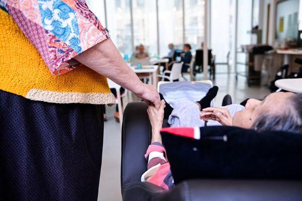 Une résidente d'EHPAD tient la main d'une autre résidente lors de la crise du Covid.