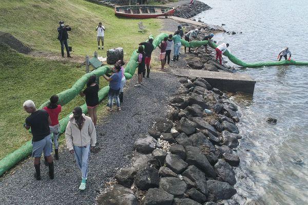 Des volontaires mettent en place un barrage flottant fabriqué localement