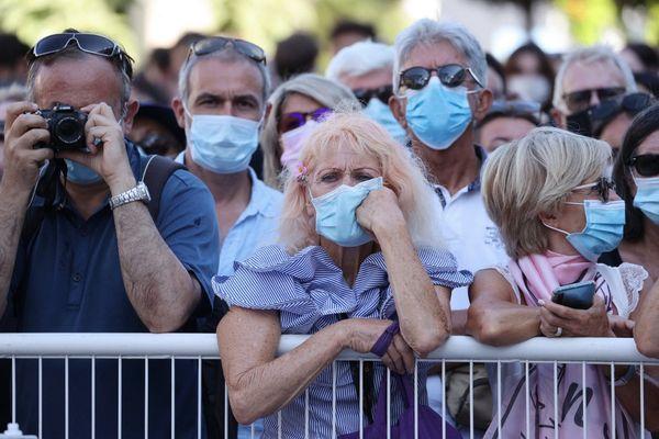 """Des festivaliers masqués attendent l'arrivée des acteurs du film """"Benedetta"""" pour sa projection au 74e festival de Cannes, le 9 juillet 2021."""