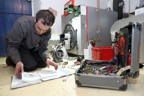 Un chauffagiste répare une chaudière une fioul.