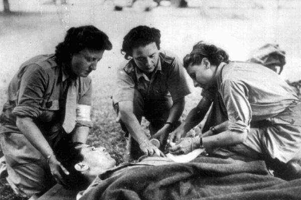 image d'illustration- Trois Rochambelles de la Division Leclerc soignent un blessé sur un brancard.