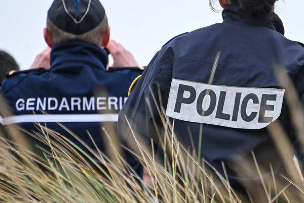Un gendarme et un policier observant la côte à Oye-Plage, près de Calais.