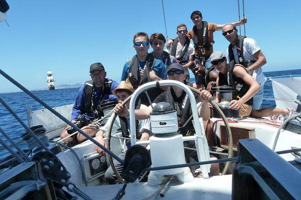 L'équipage de K8, constitué d'élèves du Lycée maritime de La Rochelle. Derrière eux, l'Hermione, toutes voiles dehors.