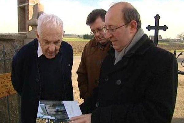 Les auteurs Bernard Xibaut et Jean-François Kovar présentent leur livre à l'ancien prêtre de l'église de Hipsheim.