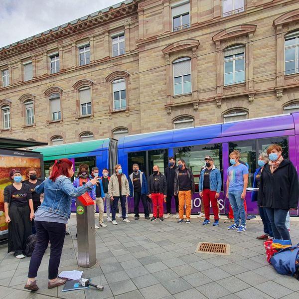La chorale LGBTQIA+ de Strasbourg, Pelicanto, chante pour inaugurer le tramway arc-en-ciel. La maire de Strasbourg compte parmi ses membres : un beau symbole.