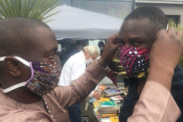 Amadou Dembélé, l'un des couturiers bénévoles, explique comment mettre le masque.