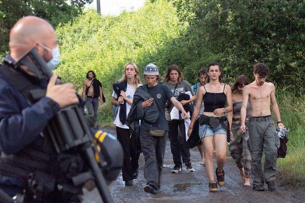 Des policiers évacuent des fêtards après une rave party illégale dans un champ à Redon, le 19 juin 2021