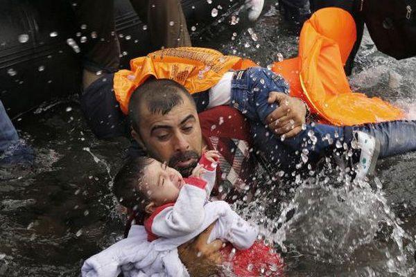 Un Syrien avec ses deux enfants tentant de débarquer après la traversée depuis la Turquie. Île de Lesbos, 24 septembre 2015. © Yannis Behrakis / Reuters