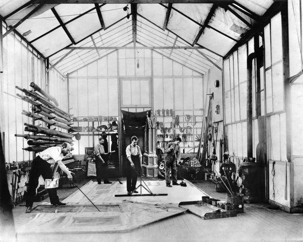 Georges Méliès à gauche, dans le Studio A peignant un décor au sol. Photographie prise au début des années 1900