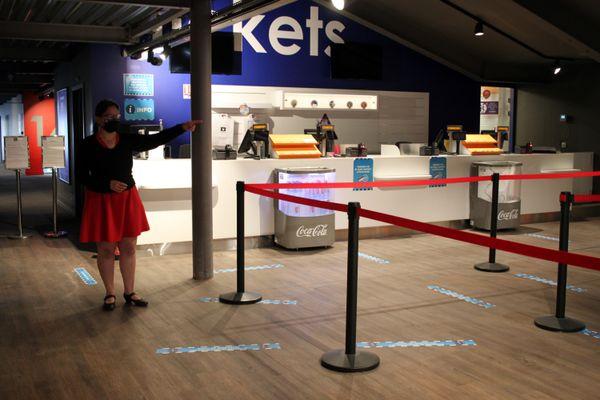Edwige Dzwierzynski indique le sens de circulation au cinéma Kinepolis à Rouen. Les marquages au sol et les affiches rappellent les mesures barrières.