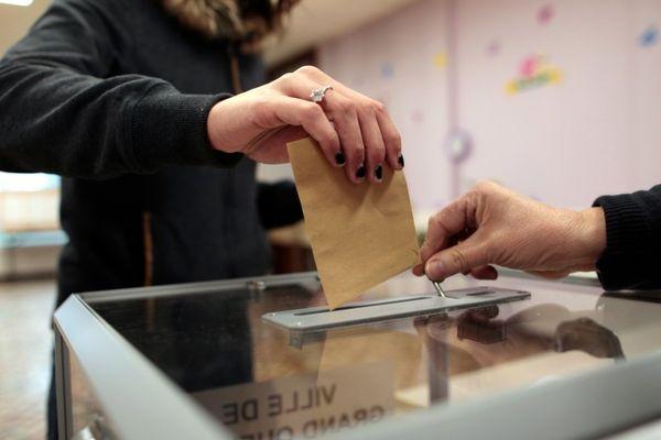Un bulletin de vote glissé dans l'urne (illustration).