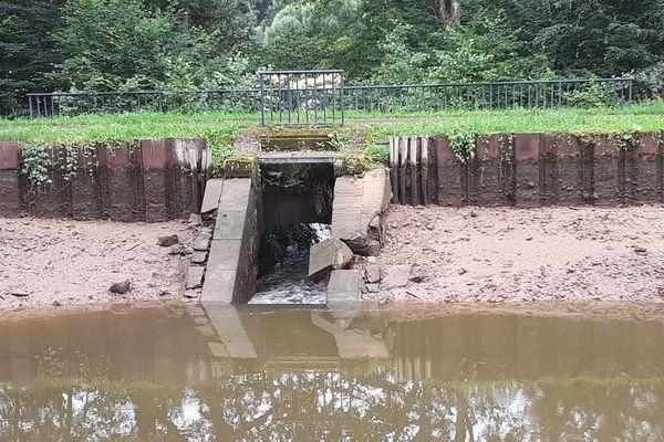 Des pierres ont été emportées au pied du déversoir aménagé sur le canal des Vosges à Pont-du-Bois, créant des infiltrations d'eau.