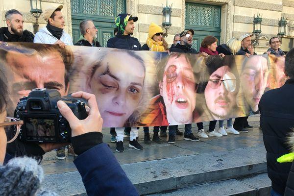Ces personnes brandissent une banderole, avec les photos de plusieurs manifestants, qui auraient été blessées lors de précédents rassemblements de gilets jaunes.