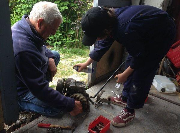 """Titouan et son grand-père réunis autour du moteur de la """"Toujours contente""""."""
