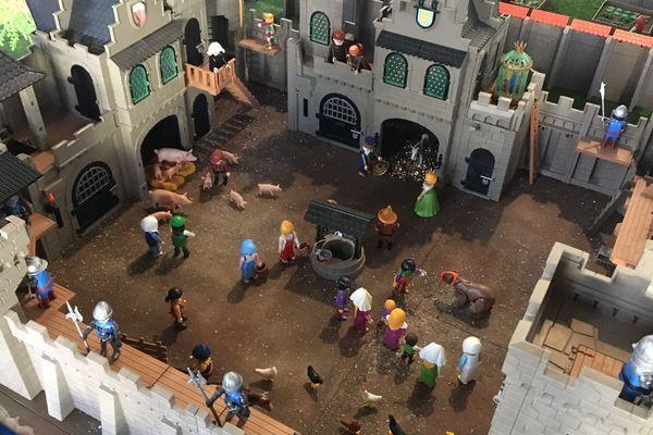 Une scène de vie médiévale en Playmobil se tient dans la cour d'un château fort.