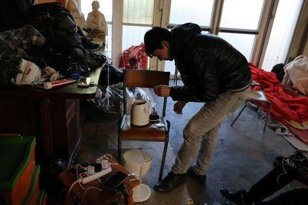 A migrant from Afghanistan prepares tea in the premises of a former church where sixty migrants, hoping to take a ferry from Cherbourg to Portsmouth in Britain, live in Cherbourg-Octeville, northwestern France, on March 3, 2016.