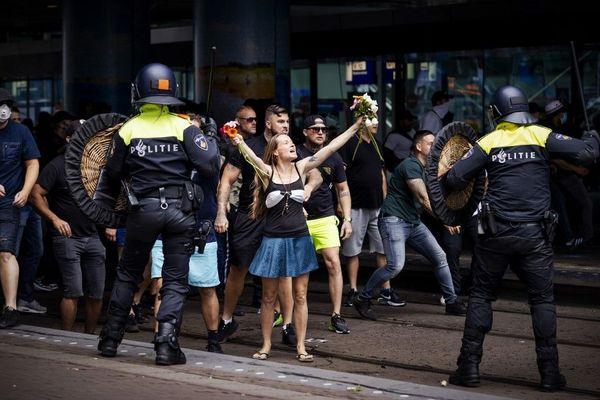 Une femme brandit des fleurs au milieu des heurts entre policiers et certains manifestants à La Haye dimanche.