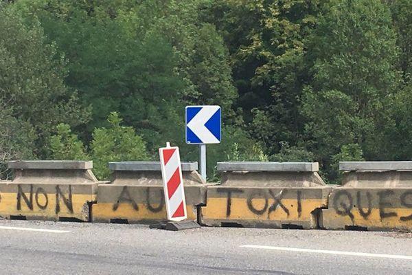 """Sur les lieux de l'accident, de nouveaux plots ont été installés pour signaler le virage, et une inscription taguée : """"non aux toxiques""""."""