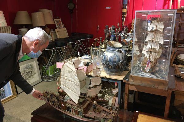 Le commissaire-priseur Thierry Collet estime une maquette de jonque asiatique, dans les réserves de l'hôtel des ventes de la Porte de Mars.