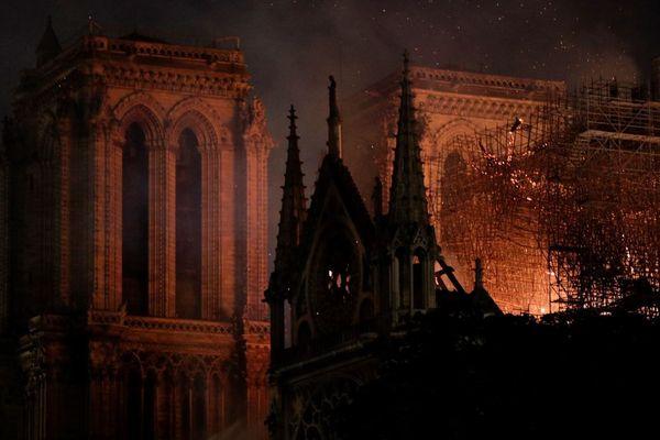 Dans l'obscurité, les flammes ravagent la cathédrale Notre-Dame de Paris.