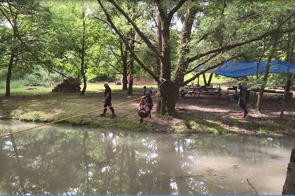 Les stagiaires doivent traverser un cours d'eau suspendus à une corde : pour survivre il faut du physique, et maîtriser sa peur.
