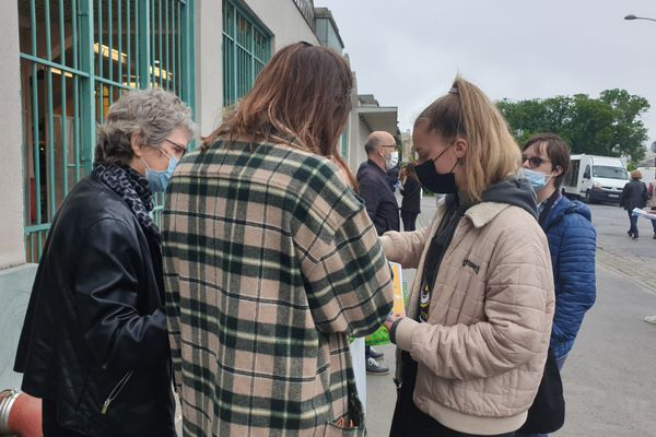 L'une des bénévoles explique le projet à des passants.