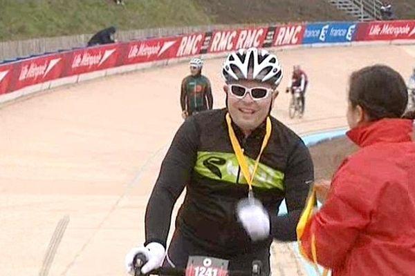 Un cycliste amateur reçoit sa médaille à l'arrivée, sur le vélodrome de Roubaix.