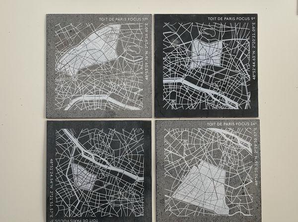 """Des fragments de feuilles de zinc illustrées par """"Toit de Paris"""" avec un plan de la capitale sur lequel figurent différents arrondissements. Pour les plus curieux désirant connaître l'endroit exact d'où la feuille de zinc originelle provient, les coordonnées géographiques l'indiquent sur le côté."""