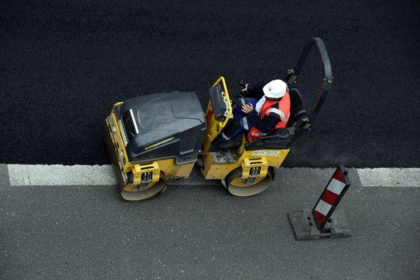 Un ouvrier lisse le bitume sur un chantier - Photo d'illustration