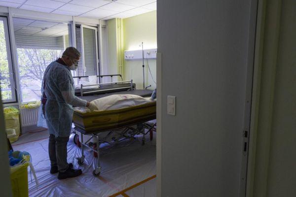 ILLUSTRATION. Des employés de compagnie funéraire sortent le cercueil d'une victime de la Covid-19 dans un hôpital de Mulhouse. (5 avril 2020)