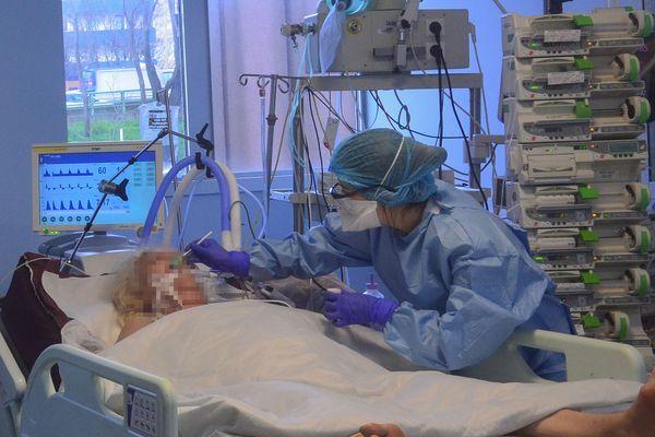 Une infirmière au chevet d'un patient atteint du COVID-19 à l'unité de soins intensifs de l'Hôpital Bichat, AP-HP, à Paris, le 13 mars 2020.