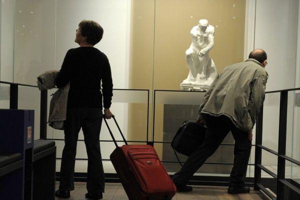 """Des passagers passent devant """"Le Penseur"""" de Rodin dans l'espace culturel de l'aéroport de Roissy Charles-de-Gaulle."""