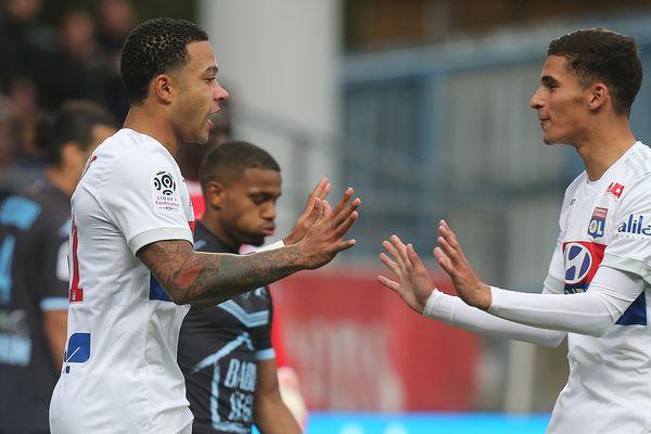 L'attaquant lyonnais Memphis Depay (L) célèbre avec son coéquipier Houssem Aouar après avoir marqué lors du match de Ligue 1 entre Troyes et Lyon au Stade de l'Aube à Troyes le 22 octobre 2017.