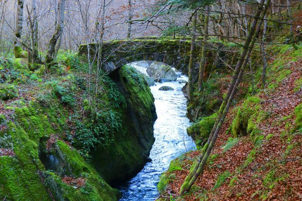 Une rivière sous un pont romain en automne