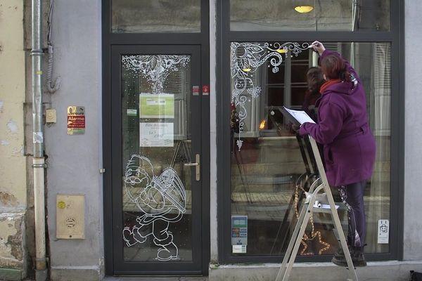 Une commerçante décore sa vitrine pour Noël