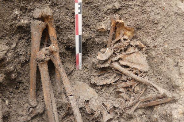 Le deuxième corps, celui d'une femme, est adossé sur la paroi de la fosse, le buste penché et les genoux repliés vers le côté droit.