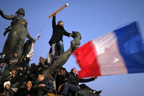 """Après la dispersion du cortège en hommage aux victimes des attentats dimanche 11 janvier 2015, de nombreux participants sont restés sur différentes places parisiennes, comme ici, place de la Nation, où a été prise cette photo vite baptisée """"Le crayon guidant le peuple"""" sur les réseaux sociaux."""