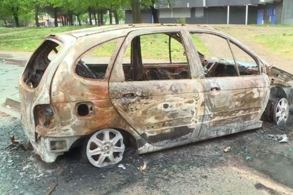 Une carcasse de voiture incendiée au pied d'un immeuble du quartier de la Reynerie à Toulouse.