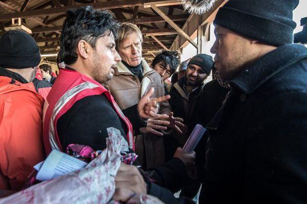 """Pascal Brice (le blond au centre) discute avec un migrant afghan, près de la """"Jungle"""" de Calais."""