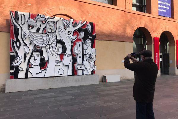 """Un homme photographiant une oeuvre de Fernand Léger dans la cour du musée des Abattoirs à Toulouse. """"Les femmes au Perroquet"""", 1952 (bas-relief en bronze polychrome)"""