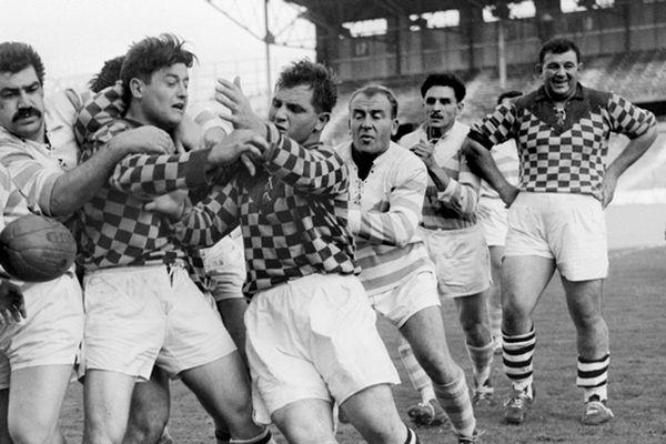 Le poids lourd Robert Soro  (à droite de l'image) s'amuse en regardant François Varenne (moustaches) du Racing en action contre les joureus de Romans, le 08 novembre 1963, lors du match de rugby à XV Racing Club de France / Romans à Colombes.