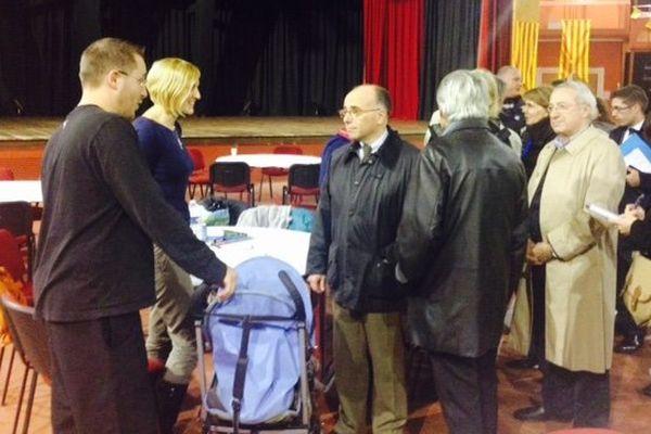 Le ministre de l'intérieur Bernard Cazeneuve avec des sinistrés, salle du dôme à Rivesaltes
