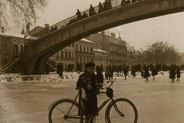 Ce 22 janvier 1914, une jeune fille tient un vélo debout sur le canal gelé. Au second plan des groupes d'individus et la passerelle des Soupirs avec des passants.