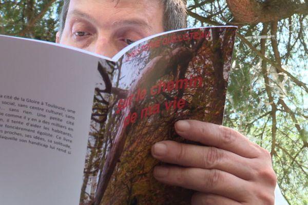 """Christophe Guilloteau, en train de lire son propre ouvrage : """"sur le chemin de ma vie""""."""