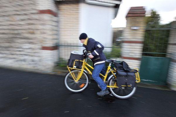 Un facteur effectue une tournée à vélo à Caen. Photo d'illustration.