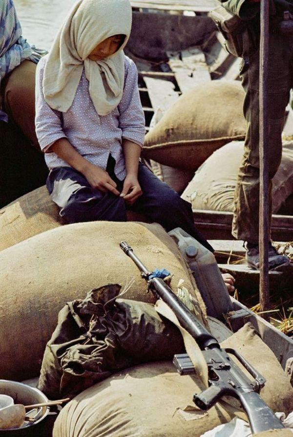 Vietnam, 1972. Delta du Mékong. Une jeune fille attend d'être « relocalisée » par l'armée sud-vietnamienne. La stratégie de la terre brûlée visait à priver le Vietcong de l'aide de la population.