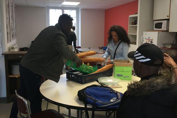 Les repas pour 20 personnes sont livrés tous les jours à midi : Valérie Marchau, travailleuse sociale et les usagers les réceptionnent;