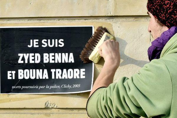 Un homme colle une affiche de soutien aux familles de Zyed et Bouna, en marge du procès qui s'est tenu à Rennes du 16 au 20 mars 2015.