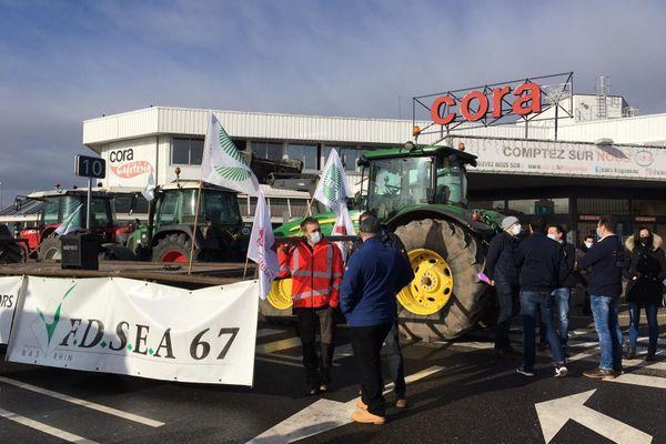 Une centaine d'agriculteurs, venus avec une trentaine de tracteurs, sont stationnés sur le parking du supermarché Cora à Hagueneau pour sensibiliser les consommateurs le 17 février 2021.